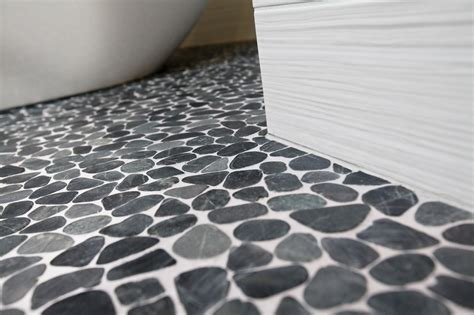 grandiose charcoal pebble shower floor with random sized as well as white ceramic wall tiled as