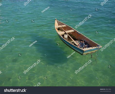 Row Boat On Water by Small Row Boat Floating On Clear Water Stock Photo
