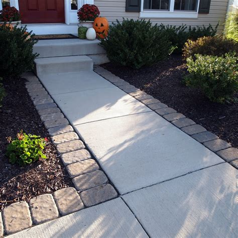 adding pavers around a standard concrete walkway can give