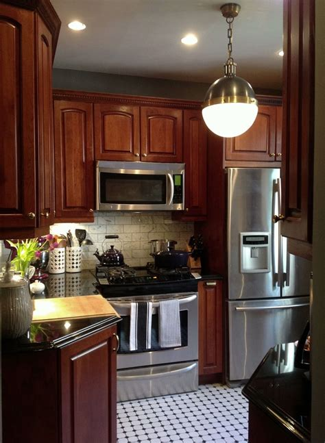 cherry cabinets with gray countertops cherry wood cabinets black white hexagon tiles hicks