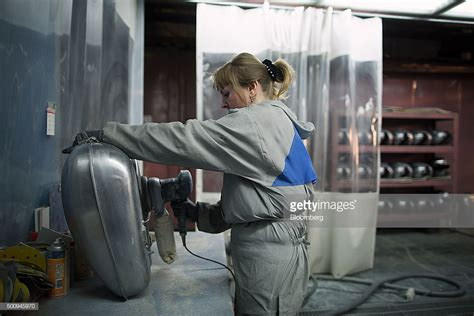 A Female Worker Polishes The Steel Fuel Tank Of A