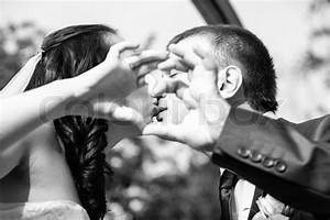 Black and white portrait of kissing bride and groom ...