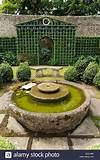 Trellis with boxed hedges and water feature in an English english garden fountains water features