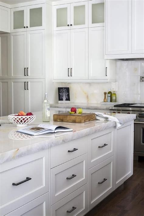 chic white kitchen features stacked white shaker cabinets