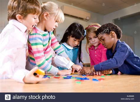 preschool pictures preschool children working together on puzzle stock photo 981