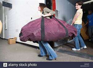 Young woman carrying a huge traveling bag Stock Photo ...