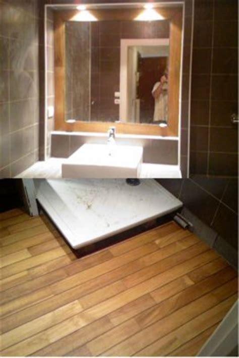 voila une salle de bain avec un parquet pont de bateau l entourage du miroir assorti de