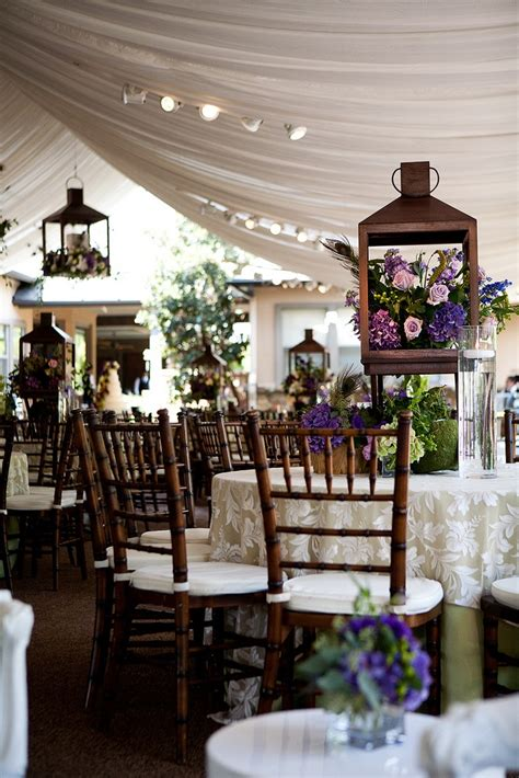 an olive green linen with a floral overlay and mahogany chiavari chairs wedding reception