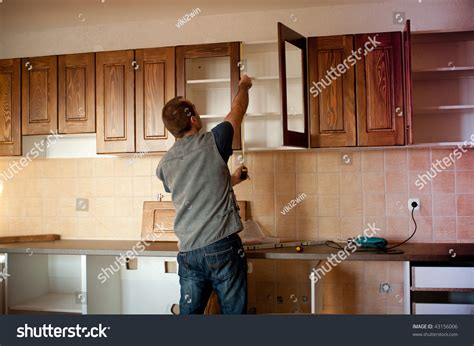 carpenter working   kitchen cabinets stock photo