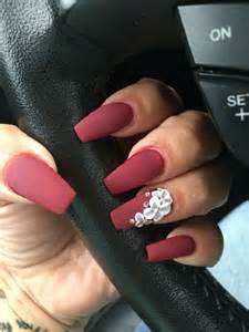 Matte shade of red with flower on coffin nails the