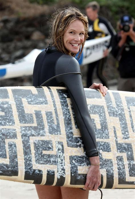 Elle Macpherson Surfing In Black Suit On A Beach In Sydney