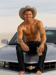 Hunky Cowboy Sitting On A Chevy Truck With A Bottle Of