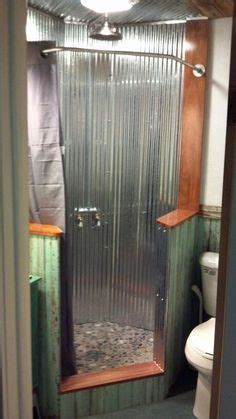 neo angle shower  corrugated tin walls  river rock