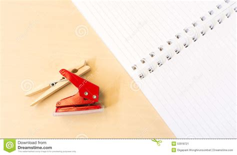 la pince a linge partition perforatrice et pince 224 linge rouges simples avec le carnet blanc ouvert dessus photo stock