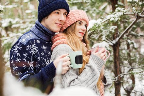 cute couple christmas montage with tea in cups in forest among fir trees stock photo image of forest
