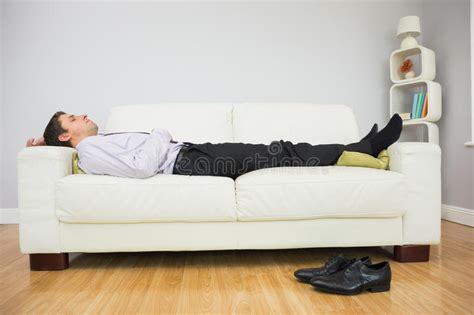 Sleeping In Living Room by Tired Businessman Sleeping On Sofa In Living Room Stock