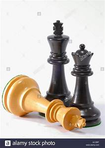 Chess pieces - a Black King and Queen remain standing. The ...