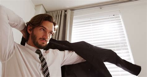 Man Getting Dressed While Looking Through Window In