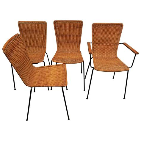 set of four rattan and iron dining chairs one with