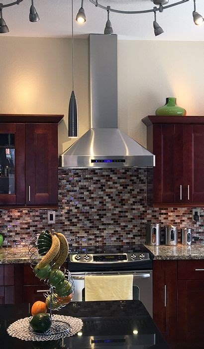beautiful red toned kitchen featuring  pljw  stainless steel wall mount range hood