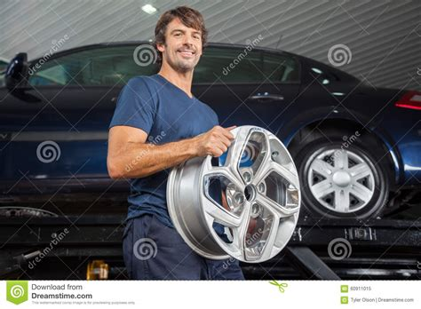 Smiling Technician Holding Alloy At Repair Shop Stock