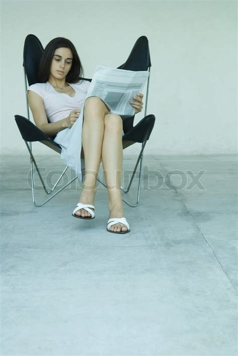 sitting in chair with legs crossed reading