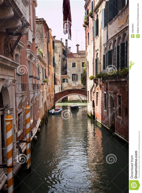 small side canal yellow poles bridge venice italy stock
