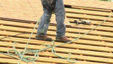 construction workers walk along the wooden slats of a roof while replacing the shingles stock