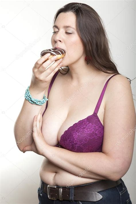 chubby woman enjoys eating  chocolate donut stock photo