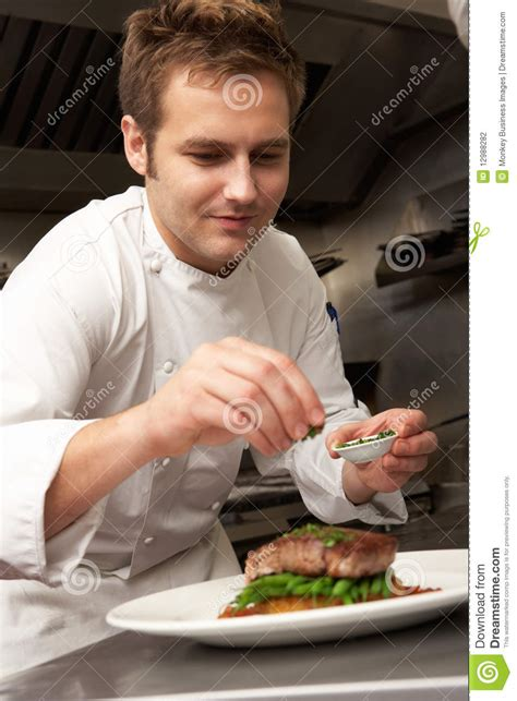 Chef Adding Seasoning To Dish In Restaurant Stock