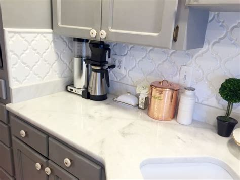 Grey kitchen cabinets, marble counters, white arabesque