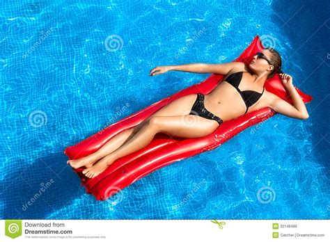 Bronzed Beauty Brunette Sunbathing In The Pool Stock Photo Image Of Relaxing Inflatable