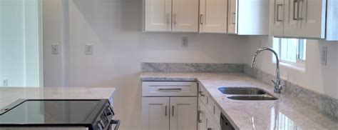 white shaker kitchen cabinets with carrara marble countertops