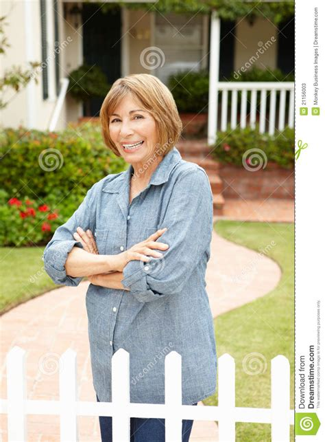 Senior Hispanic Woman Standing In Front Of Home Stock