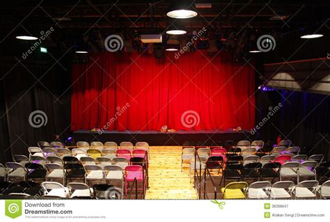 small theatre hall  red curtains stage  chairs