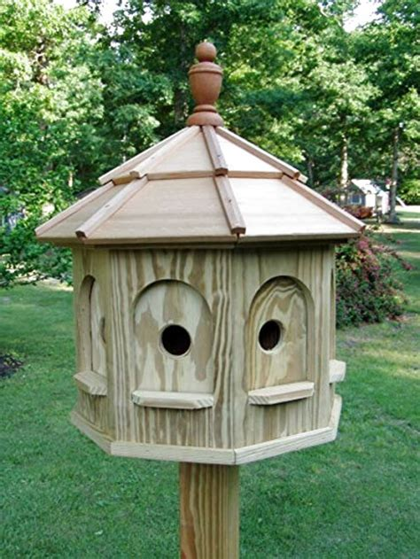 Large wooden bird houses for sale on pole Image