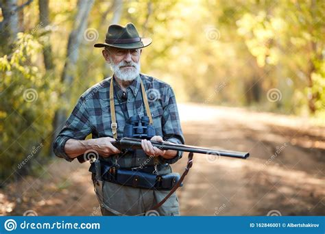 Man Holding A Rifle Hunting